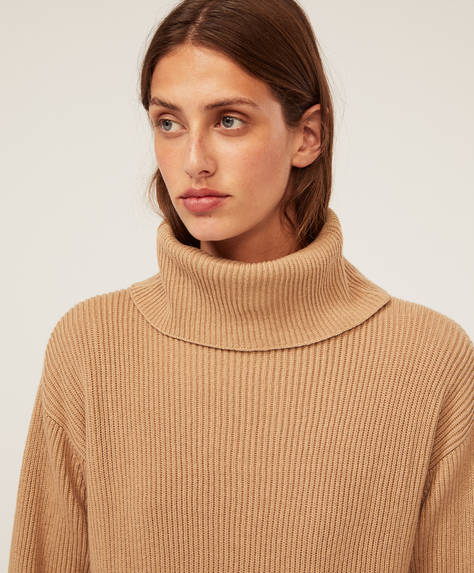 Ribbed high-neck jumper with cuffs. Side slits at the hem.