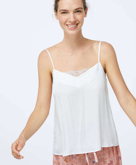 Short camisole top with V-neck. Plain fabric with lace detail at the neckline. Adjustable straps.