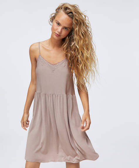 Short strappy nightdress with V-neck. Plain fabric with lace detail at the neckline. Adjustable straps.
