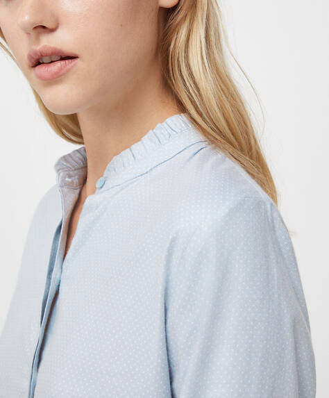 Long-sleeved shirt with button-through front. Blue cotton fabric. Cuffed sleeves.